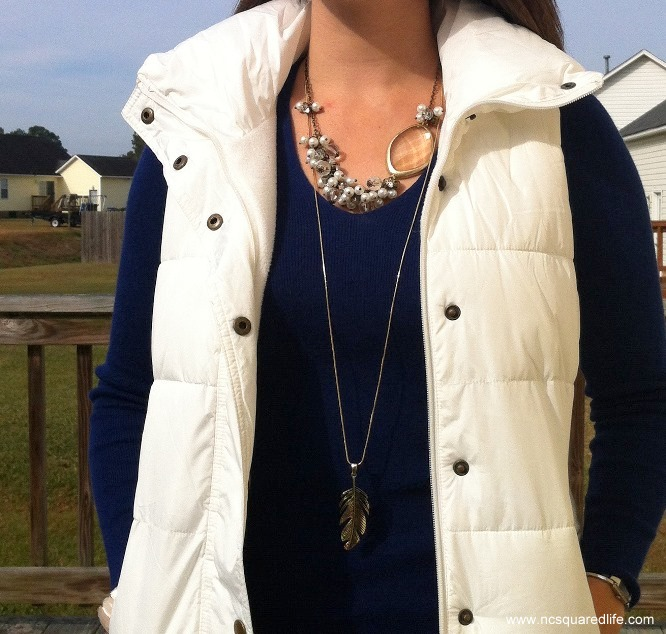white puffy vest, blue sweater, necklaces